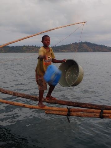 Gekonnt balanciert der Junge auf den Holzstangen von Boot zu Boot.